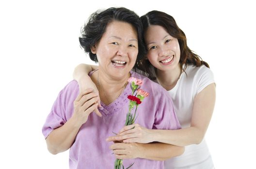 Celebrating mothers day. Portrait of Asian senior parent and adult offspring, carnation flower present from daughter, isolated on white background.