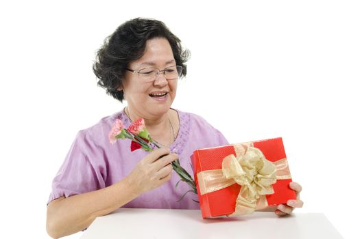 Happy mothers day concept. Portrait of 60s Asian senior adult woman receiving gift box and carnation flower from her child, isolated on white background.