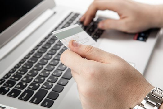 Hands holding a credit card and using laptop computer