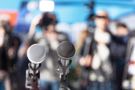 Microphone in focus, blurred camera operators in background