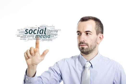 """Young businessman in blue shirt with small beard touching """"Social media"""" word cloud"""