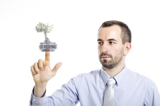 """Young businessman in blue shirt with small beard touching """"Developing"""" word cloud"""