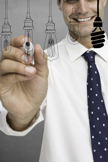 Composite image of businessman is drawing light bulb