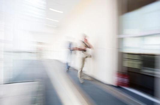 A motion blurred background image of an interior of hospital, airport or other with some human figures.