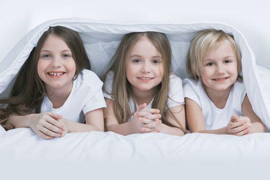 Three children under blanket