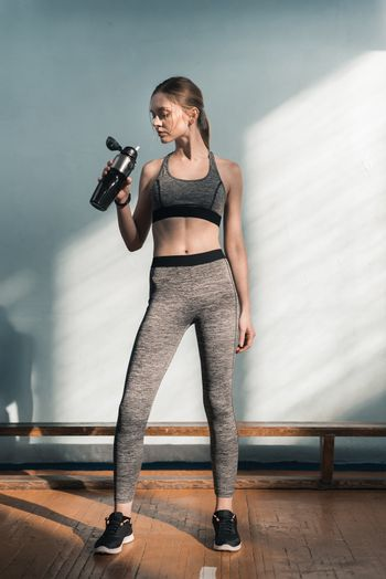 sporty woman drinking water from sports bottle after training