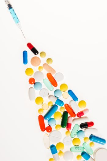 Close-up view of colorful pills and syringe on white, medicine and healthcare concept