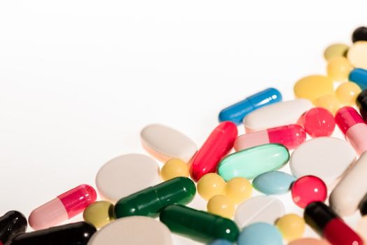 Pile of colorful pills and capsules on white background, medicine and healthcare concept