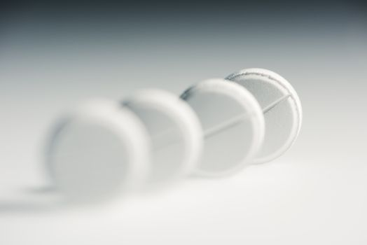 Close-up view of round white medical tablets in row, medicine and healthcare concept