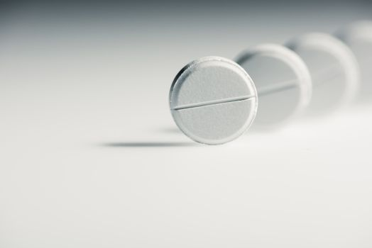 Round white medical tablets on grey background, medicine and healthcare concept