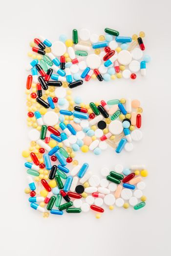 Top view of letter E made from medical pills and capsules, medicine and healthcare concept
