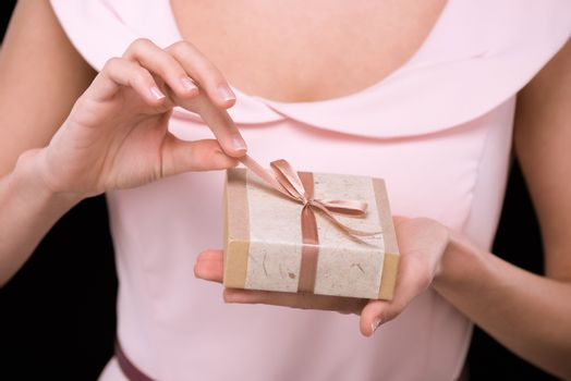Close-up partial view of woman in pink dress holding gift box on black, international womens day concept