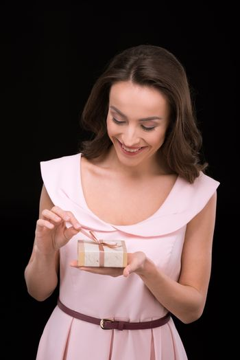 Young smiling woman in pink dress holding gift box on black, international womens day concept