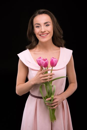 Beautiful young woman in dress holding pink tulips and smiling at camera, international womens day concept