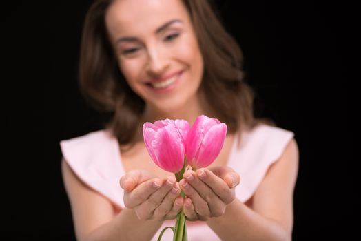 Young smiling woman holding beautiful pink tulips on black, international womens day concept