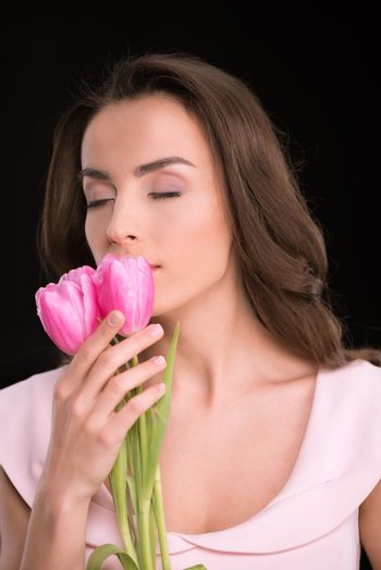 Beautiful young woman with closed eyes smelling pink tulips on black, international womens day concept