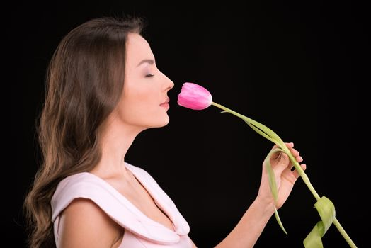 Side view of beautiful young woman with closed eyes smelling tulip flower on black, international womens day concept