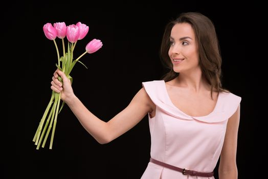 Happy young woman in dress holding pink tulips and looking away on black, international womens day concept