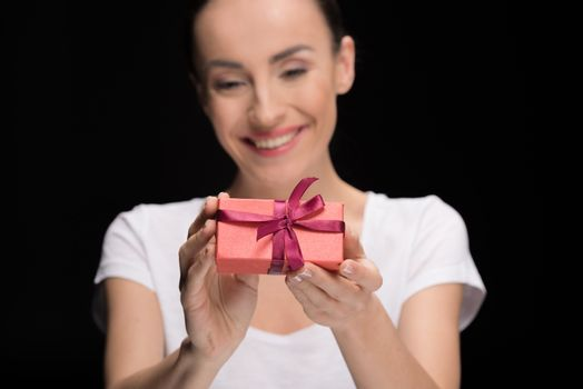portrait of smiling woman showing gift on black, focus on foreground, international womens day concept