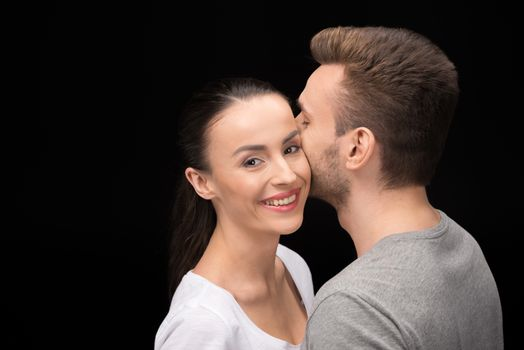 portrait of smiling woman looking to camera while bonding to man on black