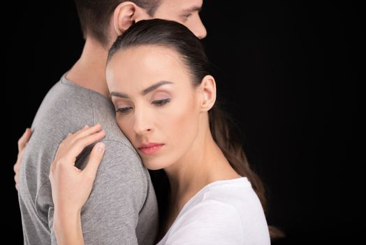 portrait of pensive woman bonding to man and looking away on black