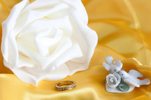 flowers, wedding rings and weddings favors on colour background