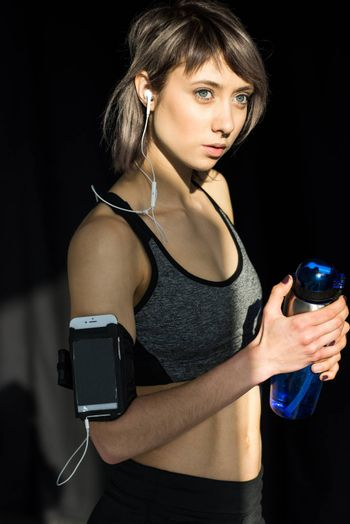 portrait of sporty woman listening music in earphones while training