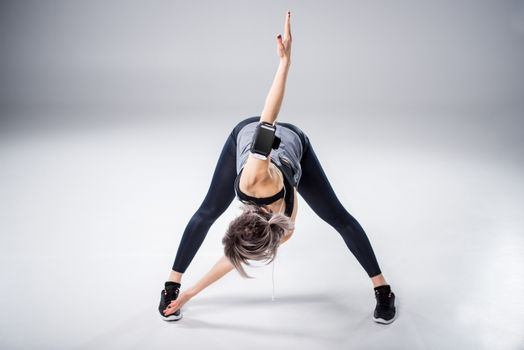 woman in sportive clothes stretching on grey