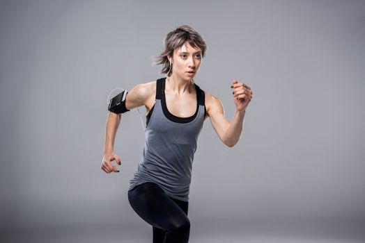 portrait of woman in sportive clothing running in earphones on grey