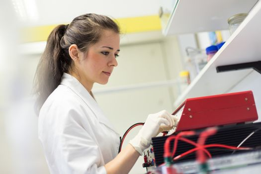 Life science researcher setting voltege on power supply to run electrophoresis.