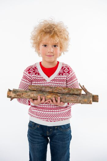 child standing with firewood in hands