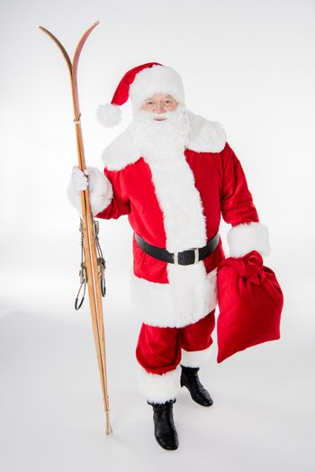 Santa Claus walking with sack and wooden skis