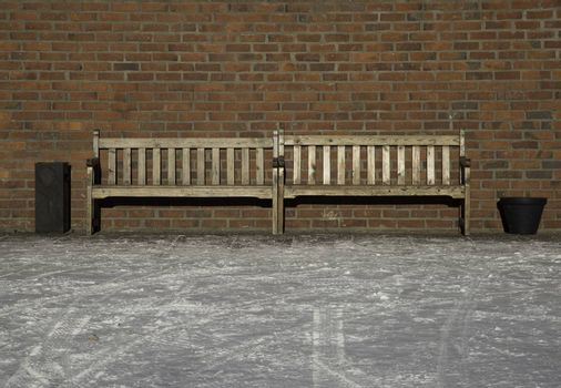 Pair of Benches by brick wall.