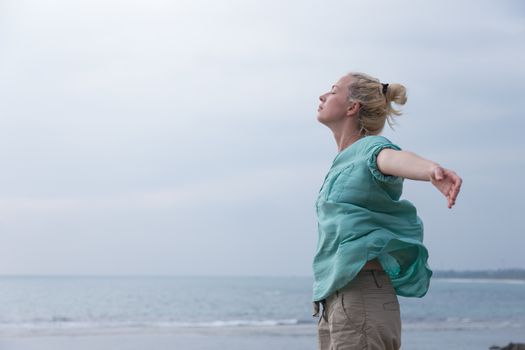 Free woman enjoying windy weather on beach on overcast day