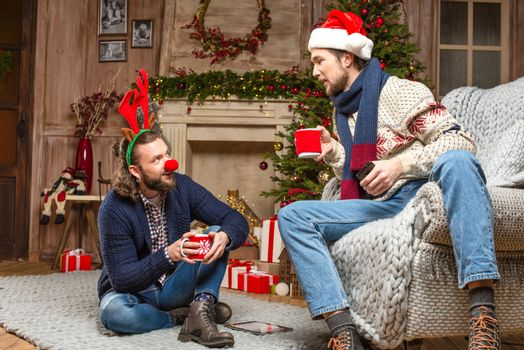 Men in christmas costumes drinking tea