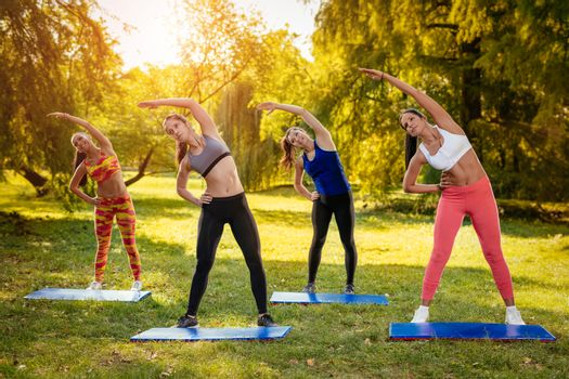 Four beautiful female friends doing stretching exercise in the park.