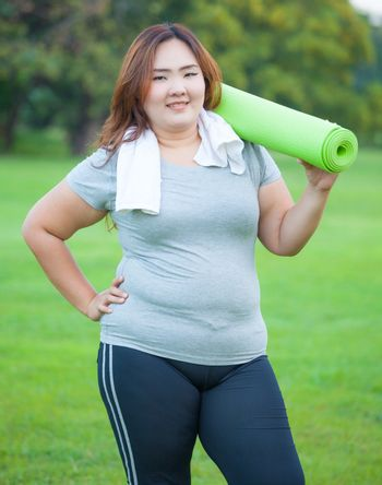 Pretty fat asian woman going to work out with her yoga mat
