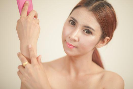 asian girl applying moisturizer on brown background