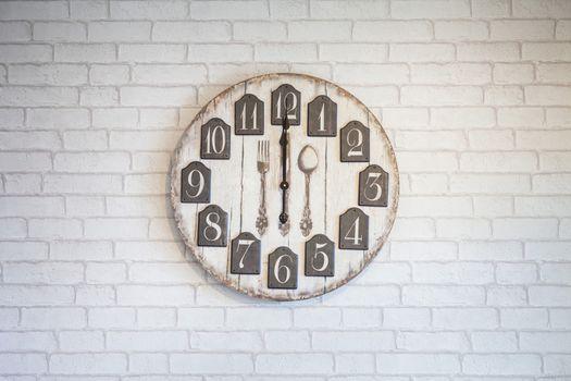 Retro vintage wall clock on white brick wall