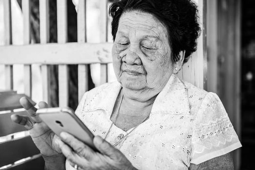Black and white image of Senior asian woman  with smart phone