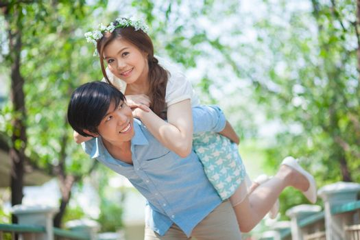 Young asian man giving a piggy back to his girlfriend in the park
