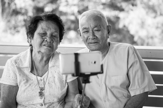 Black and white image of Happy senior couple posing for a selfie at home