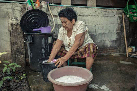 Senior asian woman washing cloths by hand