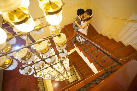 Beautiful asian young bride and groom kissing on stairs