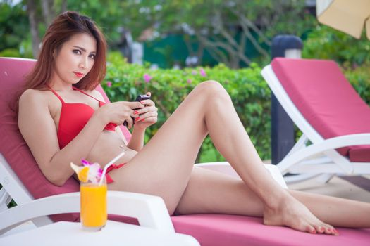 Beautiful young asian woman relaxing on sunbed with smart phone