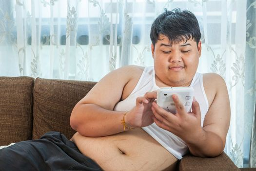 Asian fat man Relaxing in the sofa with the tablet at home
