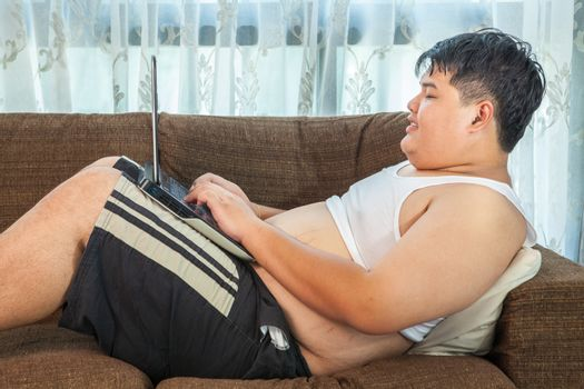 Asian fat man using laptop in home