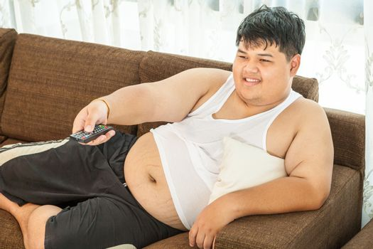 Overweight asian guy sitting on the couch with remote in hand trying to watch some TV