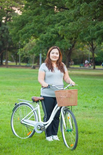 Happy fatty asian woman posing with bicycle outdoor in a park