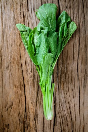 Bunch of fresh kale over old wooden background